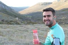 年轻臀部和现代赛跑者在山与水瓶,喝-储蓄图象 库存照片