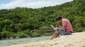 年轻自由职业者商人与在耳机的手提电脑一起使用在一个热带海滩 3840x2160 股票视频