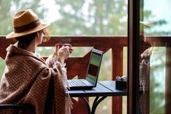 年轻自由职业者妇女坐在与膝上型计算机和饮用的茶的大阳台 库存图片