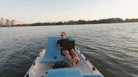 年轻自由职业者研究在小船的计算机 遥远的事务 被动收入 股票视频