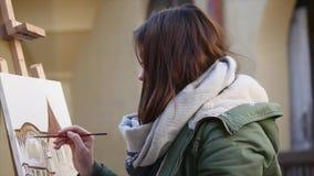 年轻艺术家凹道在城市 绘在街道上的艺术家画 学生老欧洲人的油漆大厦 股票录像