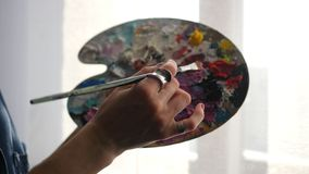 年轻艺术家混合在刷子颜色politrila的油漆, HD 免版税库存图片