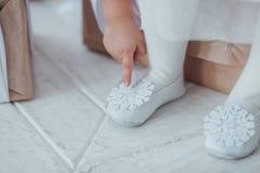 年轻芭蕾舞女演员腿特写镜头,在有雪花装饰的pointe鞋子坐在白色木地板背景 指向 免版税库存照片