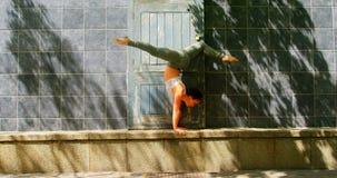 年轻芭蕾舞女演员舞蹈家实践的手倒立对墙壁4k 股票录像