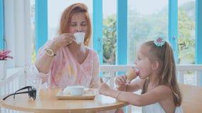 年轻花费在一个咖啡馆的母亲和她的小女儿时间与冰淇凌 股票录像