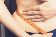 年轻苗条女孩测量腰部,特写镜头 六十厘米 库存照片