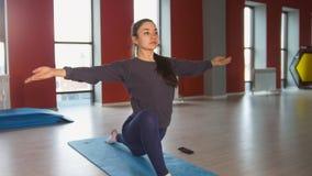 年轻苗条妇女在健身屋子里执行在地毯的舒展的锻炼 免版税库存照片