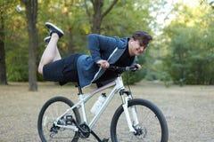 年轻英俊白种人人微笑在绿色公园执行特技腿在自行车 危险的把戏 白色无线耳机,c 图库摄影
