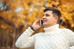 年轻英俊的人坐在秋天公园和谈话由电话 商人叫给某人由智能手机 免版税库存照片