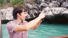 年轻英俊的人拍与电话的照片在小船旅行反对天蓝色的海湾的岩质岛 慢的行动 1920x1080 股票视频