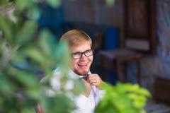 年轻英俊的人画象有佩带蝶形领结和摆在城市街道的短发的 免版税库存照片