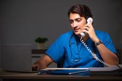 年轻英俊的医生运作的夜班在医院 免版税图库摄影