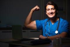 年轻英俊的医生运作的夜班在医院 库存图片