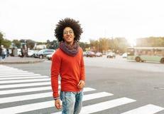 年轻英俊的卷曲人穿过路在一条行人交叉路 一愉快的留学生对生活是微笑和满意 免版税库存照片