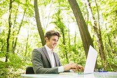 年轻英俊的商人旁边画象运作在膝上型计算机的衣服的在办公室桌上在绿色森林公园 到达天空的企业概念金黄回归键所有权 库存图片