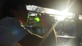 年轻英俊的商人用在室外咖啡馆的智能手机饮用的啤酒在与惊人的lense火光作用的日落期间 股票视频