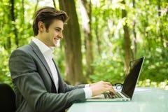 年轻英俊的商人画象衣服的在膝上型计算机在办公室桌上在绿色森林公园 到达天空的企业概念金黄回归键所有权 免版税库存照片