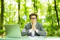年轻英俊的商人画象运作在膝上型计算机的衣服的在办公室桌上与在绿色森林公园祈祷手 事务c 免版税库存图片