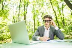 年轻英俊的商人画象运作在膝上型计算机的衣服的在办公室桌上在绿色森林公园 到达天空的企业概念金黄回归键所有权 库存图片