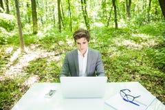 年轻英俊的商人画象运作在膝上型计算机的衣服的在办公室桌上在绿色森林公园 到达天空的企业概念金黄回归键所有权 库存照片