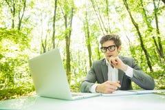 年轻英俊的商人画象运作在膝上型计算机的衣服的在办公室桌上在绿色森林公园 到达天空的企业概念金黄回归键所有权 免版税图库摄影