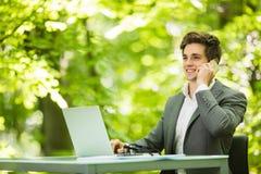 年轻英俊的商人画象运作在膝上型计算机的衣服的在办公室桌上在绿色森林公园 到达天空的企业概念金黄回归键所有权 免版税库存图片