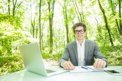 年轻英俊的商人画象运作在膝上型计算机的衣服的在办公室桌微笑在照相机在绿色森林公园 事务c 库存图片