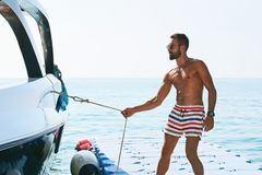 年轻英俊的回教拉扯游艇或小船的绳索的上尉佩带的短裤为了控制站立在停泊处的它 库存图片