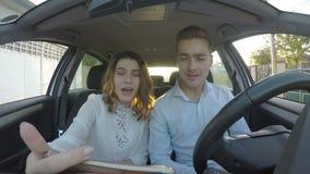 年轻英俊的夫妇有交谈低谷录影电话在巧妙的电话的汽车- 股票录像