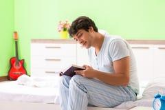 年轻英俊的学生看书在床上 免版税图库摄影