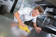 年轻英俊的男性厨师清洁餐馆厨房 库存图片