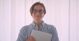 年轻英俊的白种人商人特写镜头画象在拿着膝上型计算机的玻璃的愉快地微笑常设户内  影视素材