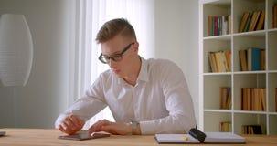 年轻英俊的白种人商人特写镜头画象在玻璃的使用户内片剂在办公室 影视素材
