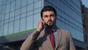 年轻英俊的看起来满意的谈话在电话的商人佩带的衣服和领带走在商业中心附近 影视素材