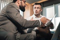 年轻英俊的经济学家讲话与雇主在会议前 库存图片