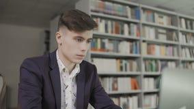 年轻英俊的行家男生坐在桌上在有膝上型计算机的lighty大图书馆里在他前面 股票视频