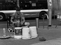 年轻英俊的街道音乐家,演奏在容器箱子的鼓在公共汽车前面的一个城市布局 免版税库存图片