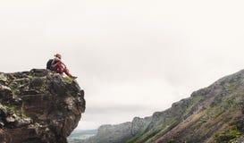 年轻英俊的远足者人坐上面和享受mounta看法  库存照片