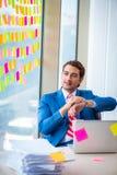年轻英俊的雇员以许多矛盾的优先权 库存照片