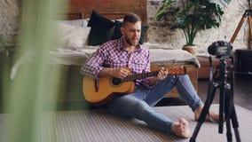 年轻英俊的音乐家普遍的博客作者记录有弹吉他和唱坐地板的照相机的录影 股票视频