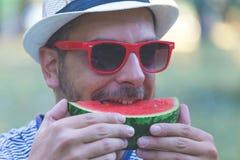 年轻英俊的食人的西瓜,拿着西瓜的人画象  免版税库存照片