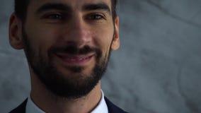年轻英俊的bussinesman接近的画象在深蓝套装神色的秘密审议和微笑慢动作 股票录像
