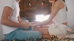 年轻获得人和的女孩坐长沙发,笑,挥动和与的乐趣光 股票录像