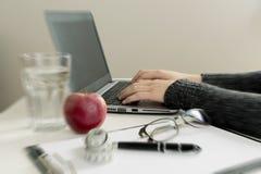 年轻营养师与在诊所的膝上型计算机一起使用 减重co 免版税库存照片