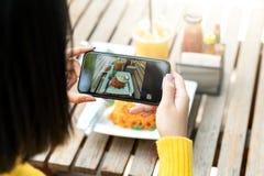 年轻行家亚裔博客作者拍食物,板材,健康食谱,午餐膳食,对故事内容的早餐份额照片在社会 免版税图库摄影