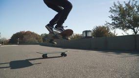年轻行家人做滑板把戏 黑暗的牛仔裤、乘坐滑板的一件轻的毛线衣和一个黑暗的帽子的少年 影视素材