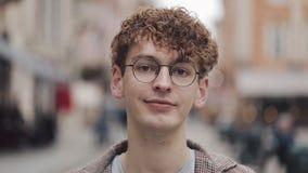 年轻行家人画象戴站立在城市街道上和调查照相机的眼镜的 旅游,旅行 影视素材