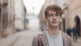 年轻行家人画象有站立在城市街道上和调查照相机的背包的 他听到音乐 影视素材