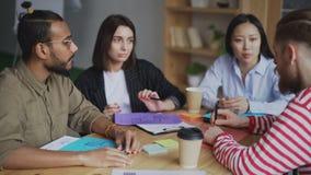 年轻行家人谈论新的起始的项目与不同种族的队在现代办公室 股票录像
