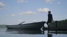 年轻行家妇女坐木码头,放松 年轻白肤金发的妇女坐在湖的一只木跳船 库存照片